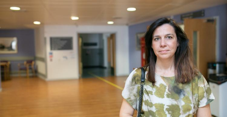 A woman standing in the main reception at hospital.
