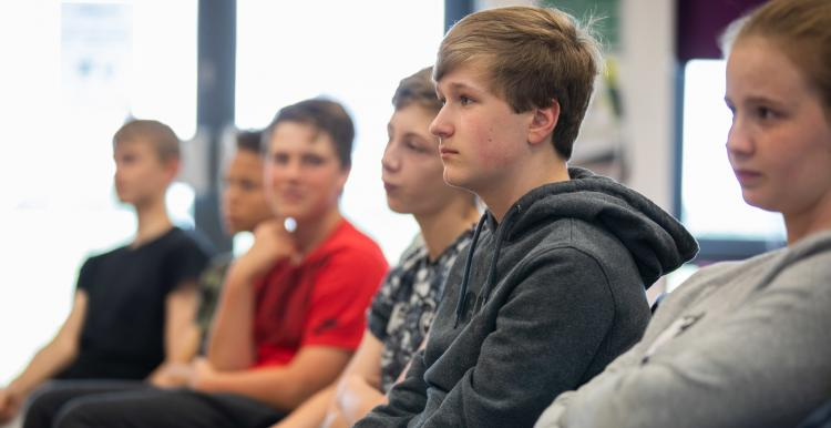 A teenage boy sitting in a row of chairs with other teenagers his age.