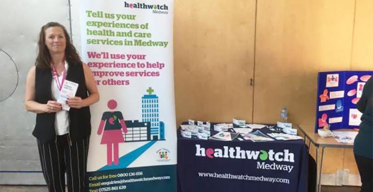 Healthwatch Medway's Debbie standing in front of our stall at the event held by One Voice