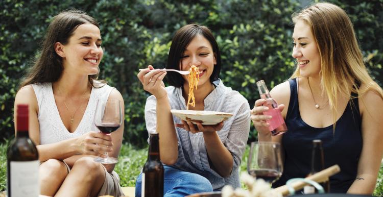Three friends joyfully eating pasta together