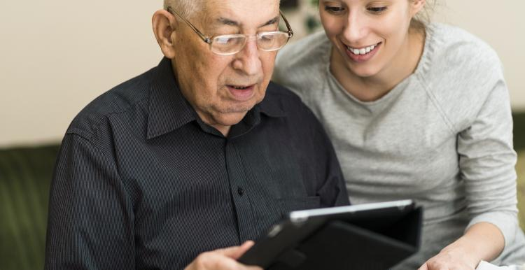 Picture of elderly man getting help to use an Ipad