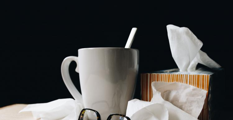 A stack of used tissues on a bedside table, next to a hot cuppa and some folded up glasses.