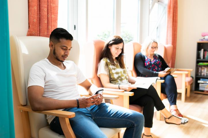 Three people sitting in an hospital waiting room, keeping themselves occupied with magazines and their smartphones