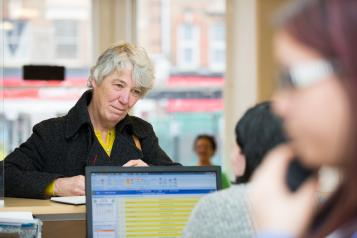 Older woman at a GP reception desk trying to book a GP appointment.