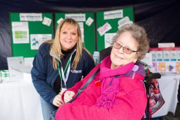 Healthwatch staff member speaking to an elderly woman in a wheelchair