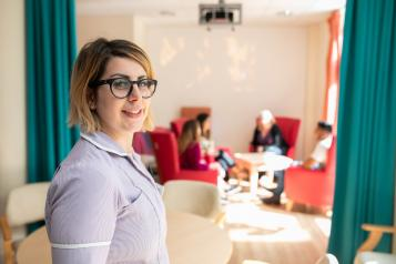 Nurse smiling at the camera. People in the background are sitting round a table chatting.