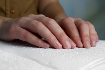 Two hands scanning over a Braille book. Image from Braille Works.