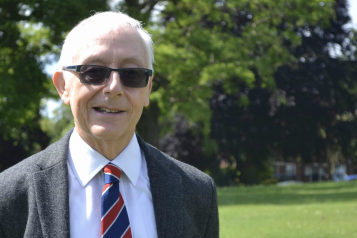 A picture of Alan smiling at the camera, standing in a park on a lovely sunny day.