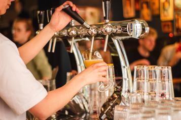 Bartender pouring a fresh pint of lager