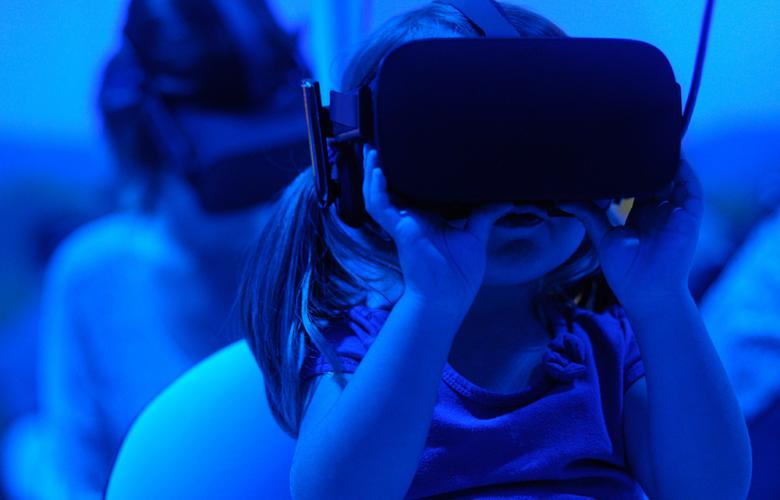 A child wearing a Virtual Reality headset. The lighting in the image is blue for a futuristic effect.