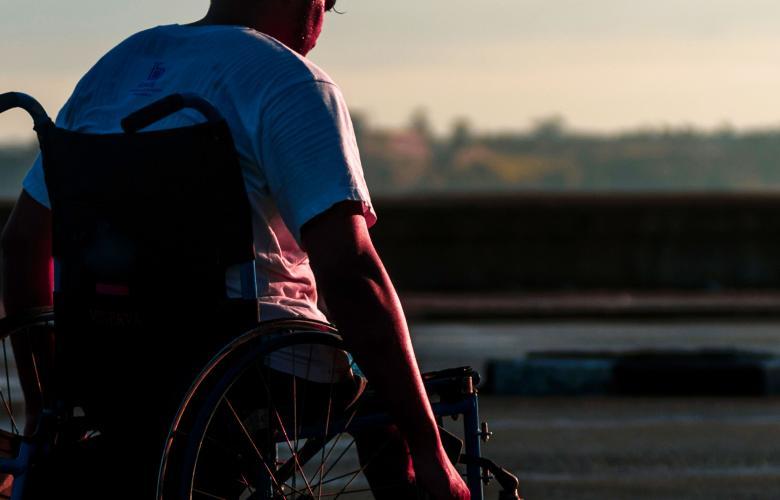 Boy pushing himself in a wheelchair.